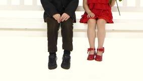 Πόδια των μικρών παιδιών, κάθονται σε μια ταλάντευση Άσπρη ανασκόπηση απόθεμα βίντεο