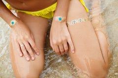 Πόδια χεριών γυναίκας με το tatoo αυτοκόλλητων ετικεττών στη θάλασσα Στοκ φωτογραφία με δικαίωμα ελεύθερης χρήσης