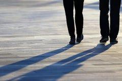 Πόδια δύο ανθρώπων που ενώνονται στο τετράγωνο Στοκ Φωτογραφίες