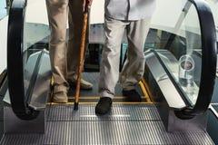 Πόδια δύο ατόμων στην έξοδο από την κυλιόμενη σκάλα Στοκ Εικόνα