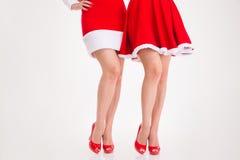 Πόδια δύο γυναικών στα φορέματα santa και τα κόκκινα παπούτσια Στοκ Φωτογραφία