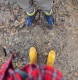 Πόδια δύο ζευγαριών στα ζωηρόχρωμα gumboots Στοκ φωτογραφία με δικαίωμα ελεύθερης χρήσης
