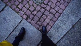Πόδια δύο κοριτσιών που περπατούν κατά μήκος του δρόμου πετρών στις μπότες στην πόλη τη δροσερή χειμερινή ημέρα υπαίθρια απόθεμα βίντεο