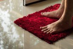 Πόδι ατόμων στο κόκκινο doormat Στοκ Εικόνα