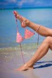 Πόδι γυναικών που κρατά το ρόδινο στηθόδεσμο απομονωμένο σε εξωτικό στοκ εικόνες