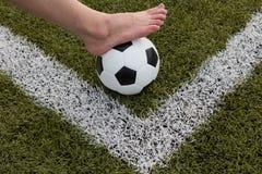 Πόδι κοριτσιών στη σφαίρα ποδοσφαίρου στον πράσινο τομέα Στοκ Φωτογραφία