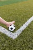 Πόδι κοριτσιών στη σφαίρα ποδοσφαίρου στον πράσινο τομέα Στοκ Εικόνες