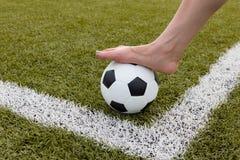 Πόδι κοριτσιών στη σφαίρα ποδοσφαίρου στον πράσινο τομέα Στοκ Εικόνα