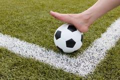 Πόδι κοριτσιών στη σφαίρα ποδοσφαίρου στον πράσινο τομέα Στοκ εικόνες με δικαίωμα ελεύθερης χρήσης