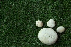 Πόδι σκυλιών ` s φιαγμένο από πέτρα χαλικιών στην πράσινη χλόη Στοκ εικόνα με δικαίωμα ελεύθερης χρήσης