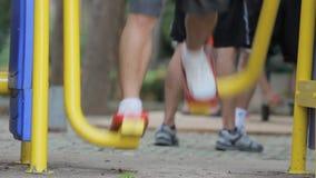 Πόδι των ανθρώπων που ασκούν στον εξοπλισμό γυμναστικής στο πάρκο φιλμ μικρού μήκους