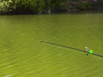 Πόλος αλιείας με τα κουδούνια στον πράσινο ήρεμο ποταμό, γραμμή κατώτατης αλιείας Στοκ Εικόνες