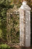 Πύλη επεξεργασμένου σιδήρου με τον άσπρο τοίχο σε έναν κήπο στοκ εικόνες
