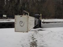 Πύλη κλειδαριών το χειμώνα με το χιόνι στο έδαφος και τον πάγο στο κανάλι νερού, Kennet και Avon στοκ εικόνα