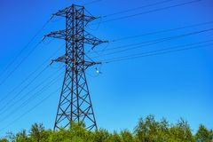 Πύργοι ηλεκτροφόρων καλωδίων ενάντια του μπλε ουρανού στοκ εικόνες