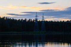 Πύργοι των ηλεκτροφόρων καλωδίων στη λίμνη, ενάντια στο σκηνικό του ηλιοβασιλέματος Στοκ Φωτογραφίες