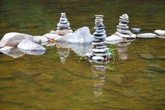 Πύργοι των μικρών χαλικιών στη μέση ενός ποταμού στοκ εικόνες