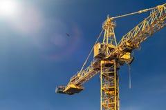Πύργος γερανών κατασκευής στις ελαφριές ακτίνες ήλιων στο υπόβαθρο του BL Στοκ Εικόνες