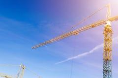 Πύργος γερανών κατασκευής στο υπόβαθρο μπλε ουρανού Γερανός και πρόοδος εργασίας οικοδόμησης Κίτρινη ανυψωτική στρόφιγγα Κενό διά στοκ εικόνες
