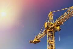 Πύργος γερανών κατασκευής στο φως ήλιων στο υπόβαθρο του μπλε SK Στοκ Φωτογραφίες