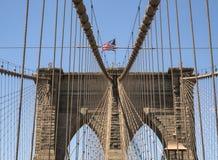 Πύργος γεφυρών του Μπρούκλιν με την ΑΜΕΡΙΚΑΝΙΚΗ σημαία Στοκ Εικόνα