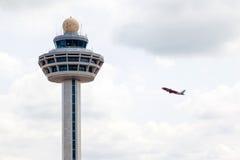 Πύργος ελεγκτών κυκλοφορίας αερολιμένων της Σιγκαπούρης Changi με το αεροπλάνο Tak Στοκ Εικόνες