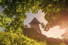 Πύργος και τοίχος του Castle Ορόσημο και προορισμός ταξιδιού Πέτρινη οχύρωση στον πράσινο λόφο στο μπλε ουρανό Προστασία και στοκ φωτογραφία με δικαίωμα ελεύθερης χρήσης