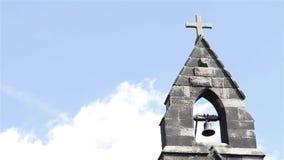 Πύργος κουδουνιών ενάντια μπλε ουρανού στη χνουδωτή εκκλησία επαρχίας σύννεφων όμορφη ελαφριά παλαιά φιλμ μικρού μήκους