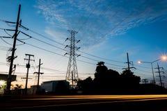 Πύργος μετάδοσης δύναμης κατά τη διάρκεια των φω'των χρόνου και αυτοκινήτων λυκόφατος Στοκ Εικόνες