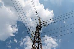 Πύργος με τα καλώδια δύναμης ενάντια στο μπλε ουρανό με τα χνουδωτά σύννεφα στοκ φωτογραφία με δικαίωμα ελεύθερης χρήσης