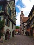 Πύργος ρολογιών και παραδοσιακά σπίτια με τις ζωηρόχρωμες προσόψεις και κεκλιμένες στέγες σε Riquewihr, Γαλλία στοκ φωτογραφία με δικαίωμα ελεύθερης χρήσης