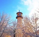 Πύργος ρολογιών σε ένα υπόβαθρο των δέντρων στο χιόνι μια ηλιόλουστη παγωμένη ημέρα Στοκ φωτογραφίες με δικαίωμα ελεύθερης χρήσης