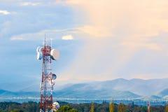 Πύργος τηλεπικοινωνιών με το υπόβαθρο σειράς βουνών με θερμό Στοκ Εικόνες