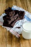 Πύργος των κομματιών σοκολάτας με το γάλα στον ξύλινο πίνακα Στοκ εικόνες με δικαίωμα ελεύθερης χρήσης