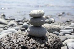 Πύργος τύμβων τριών πετρών seacoast της Μαδέρας, poise πέτρες, γλυπτό βράχου zen, ανοικτό γκρι χαλίκια, μπλε ωκεάνιο υπόβαθρο στοκ φωτογραφία