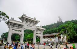 Πύλη στο Po Lin μοναστήρι με το άγαλμα Tian Tan Βούδας επάνω στο λόφο στο χωριό μεταλλικού θόρυβου Ngong, Lantau Islan Στοκ Εικόνες