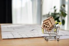 Πώληση επίπεδη ή έννοια διαμερισμάτων Λίγο κάρρο αγορών με να στηριχτεί που στέκεται στο επιτραπέζιο εσωτερικό ελαφρύ δωμάτιο με  στοκ εικόνες με δικαίωμα ελεύθερης χρήσης