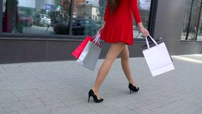 Πώληση, καταναλωτισμός: Βέβαια κυρία στα τακούνια με τις τσάντες αγορών που περπατά μετά από σε μια πόλη όμορφα θηλυκά πόδια απόθεμα βίντεο