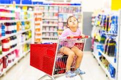 Πώληση, καταναλωτισμός και έννοια ανθρώπων - ευτυχές μικρό κορίτσι στο κάρρο αγορών στοκ εικόνα