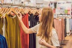 Πώληση, μόδα, καταναλωτισμός και έννοια ανθρώπων - η ευτυχής νέα γυναίκα με τις αγορές τοποθετεί την επιλογή των ενδυμάτων στη λε στοκ εικόνα με δικαίωμα ελεύθερης χρήσης