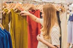 Πώληση, μόδα, καταναλωτισμός και έννοια ανθρώπων - η ευτυχής νέα γυναίκα με τις αγορές τοποθετεί την επιλογή των ενδυμάτων στη λε στοκ εικόνα