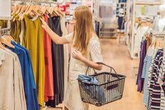 Πώληση, μόδα, καταναλωτισμός και έννοια ανθρώπων - η ευτυχής νέα γυναίκα με τις αγορές τοποθετεί την επιλογή των ενδυμάτων στη λε στοκ εικόνες