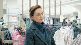 Πώληση, μόδα, καταναλωτισμός και έννοια ανθρώπων - οι αγορές γυναικών τοποθετούν την επιλογή των ενδυμάτων στη λεωφόρο ή την ενδυ απόθεμα βίντεο