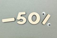 -50% πώληση των ξύλινων αριθμών για ένα γκρίζο υπόβαθρο εγγράφου στοκ φωτογραφία με δικαίωμα ελεύθερης χρήσης