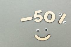 -50% πώληση των ξύλινων αριθμών για ένα γκρίζο υπόβαθρο εγγράφου Smiley στοκ φωτογραφία με δικαίωμα ελεύθερης χρήσης