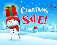 Πώληση Χριστουγέννων! Ο εύθυμος χιονάνθρωπος κρατά ψηλά το δώρο παρόν στο χειμερινό τοπίο σκηνής χιονιού Χριστουγέννων απεικόνιση αποθεμάτων