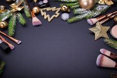 Πώληση Χριστουγέννων των καλλυντικών και των βουρτσών Σύνολο καλλυντικών με τη διακόσμηση Χριστουγέννων στο μαύρο υπόβαθρο Στοκ Φωτογραφίες