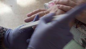 Πώς να κάνει το καρφί Υπολογισμός του UV καρφιού στίλβωση πηκτωμάτων των επαγγελματικών οδηγήσεων καρφιών στο σαλόνι closeup κίνη απόθεμα βίντεο