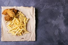Πώς το τριζάτο Κεντάκυ τηγάνισε τα φτερά κοτόπουλου με τις τηγανιτές πατάτες σε αγροτικό χαρτί για το σκοτεινό backgrond διάστημα στοκ εικόνα
