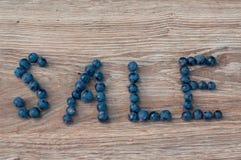 Πώληση λέξης φιαγμένη από μπλε μούρα σταφυλιών σε έναν ξύλινο πίνακα Στοκ Εικόνες